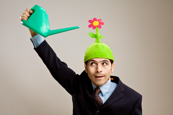 Business man wearing a flower hat and holding a watering can above his head.